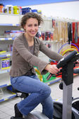Young woman on sports training apparatus in shop — Stock Photo
