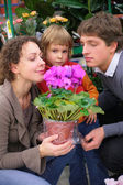 Parents and child with pot in flower shop — Stock Photo