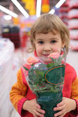 Child holds pot with flower in shop — Stock Photo
