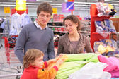 Parents with child choose fabric in shop — Stock Photo