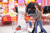 Parents roll cart with child in supermarket — Stok fotoğraf