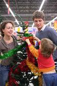 Föräldrar med barn köper julgran med dekorationer — Stockfoto