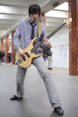 Young musician play on guitar at metro station — Stock Photo