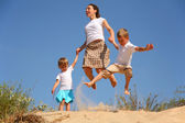 Mother with children jumping on sand — Stock Photo