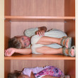 Royalty-Free Stock Photo: Two children sleeps on shelves in cabinet