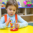 Little girl plays in kindergarten — Stock Photo #7450032