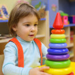 Little girl plays in kindergarten with plastic pyramid — Stock Photo
