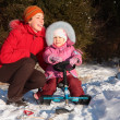 Foto Stock: Mother and daughter with snow scooter