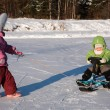 Child pulls another on snow scooter - 图库照片
