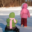 Child pulls another on snow scooter from back — Foto de Stock