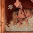 Mother behind window kisses daughter — Stock Photo