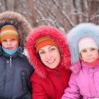 Mother with children in wood in winter - Stock Photo