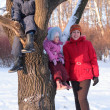 Mother with children on tree in wood in winter — Stock Photo