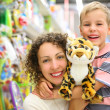 Mother and son with soft toy in shop — Stock Photo