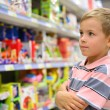 Boy looks at shelves with toys in shop - Stock Photo