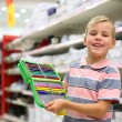 Boy with colour pencils in shop — Stock Photo