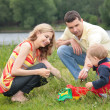 Parents play with child outdoor - Stockfoto