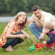 Parents play with child outdoor - Foto Stock