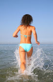 Young woman runs on water from back — Stock Photo