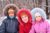 Mother with children in wood in winter — Stock Photo
