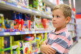 Boy looks at shelves with toys in shop — Stock Photo