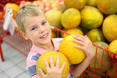 Boy with melons in shop — Stock Photo