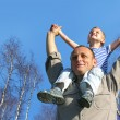 Senior with child on shoulders in front of spring birch tree col — Stock Photo