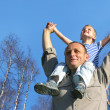 Royalty-Free Stock Photo: Senior with child on shoulders in front of spring birch tree col