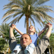 Senior with child on shoulders in front of palm tree collage — Stock Photo