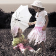 Vintage photo with two little girls with an umbrella on lawn — Stock Photo