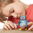 Little girl in red T-shirt plays with clockwork robot isolated o — Stock Photo #7936062