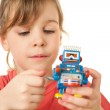 Pretty little girl in red T-shirt plays with clockwork robot iso — Stock Photo