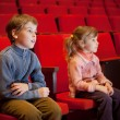 Boy and  little girl sitting on armchairs at cinema — Stok fotoğraf
