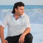 un hombre está sentado cerca del agua en la costa del mar — Foto de Stock