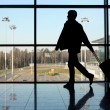 Silhouette of man with luggage walking left near window in airpo — Foto Stock