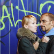 Man and woman is staying near graffiti wall. — Stock Photo