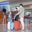 Young family with boy standing in airport hall with suitcases si — Stock Photo