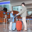 Father and son with suitcases standing in airport hall side view — Stock Photo