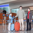 Stock Photo: Family with boy standing in airport hall with suitcases full bod
