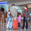 Family with boy and girl standing in airport hall with two suitc — Stock Photo