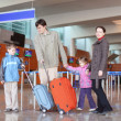 Family with suitcases walking in airport hall — Stock Photo
