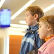Stock Photo: Little boy and girl in airport blue screens on background side v