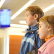 Little boy and girl in airport blue screens on background side v — Stock Photo
