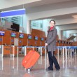 Girl with red suitcase standing in airport hall side view — Stock Photo