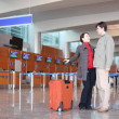 Royalty-Free Stock Photo: Man and girl with red suitcase standing in airport hall