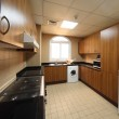 Kitchen with brown cupboards, washingmachine, cooker and fridge — Stock Photo