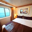 Ship cabin with big double bed and window with view on sea summe - Stock Photo