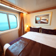 Ship cabin with big double bed and window with view on sea summe — Stock Photo #7936511