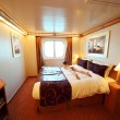 Little boy lies on big double bed in ship cabin general view sum - Stock Photo