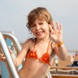 Caucasian little girl standing on cruise ship, smiling and wavin — Stock Photo